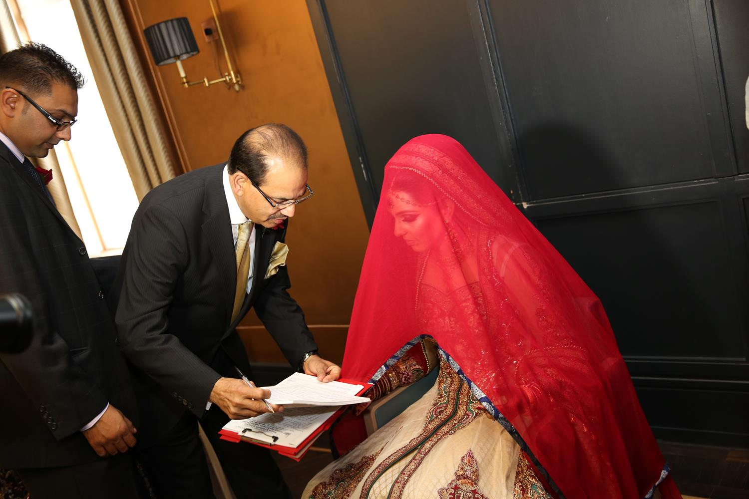 Wedding Photography of Bride signing certificate at her Asian Wedding by MAKSAM Photography London