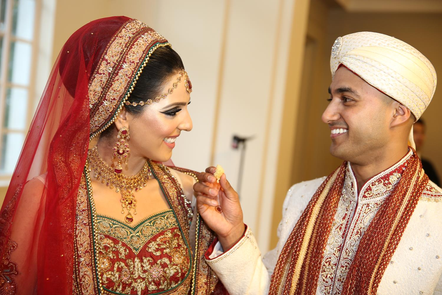 Wedding Photography of Bride and Groom feeding each other at their Asian Wedding by MAKSAM Photography London