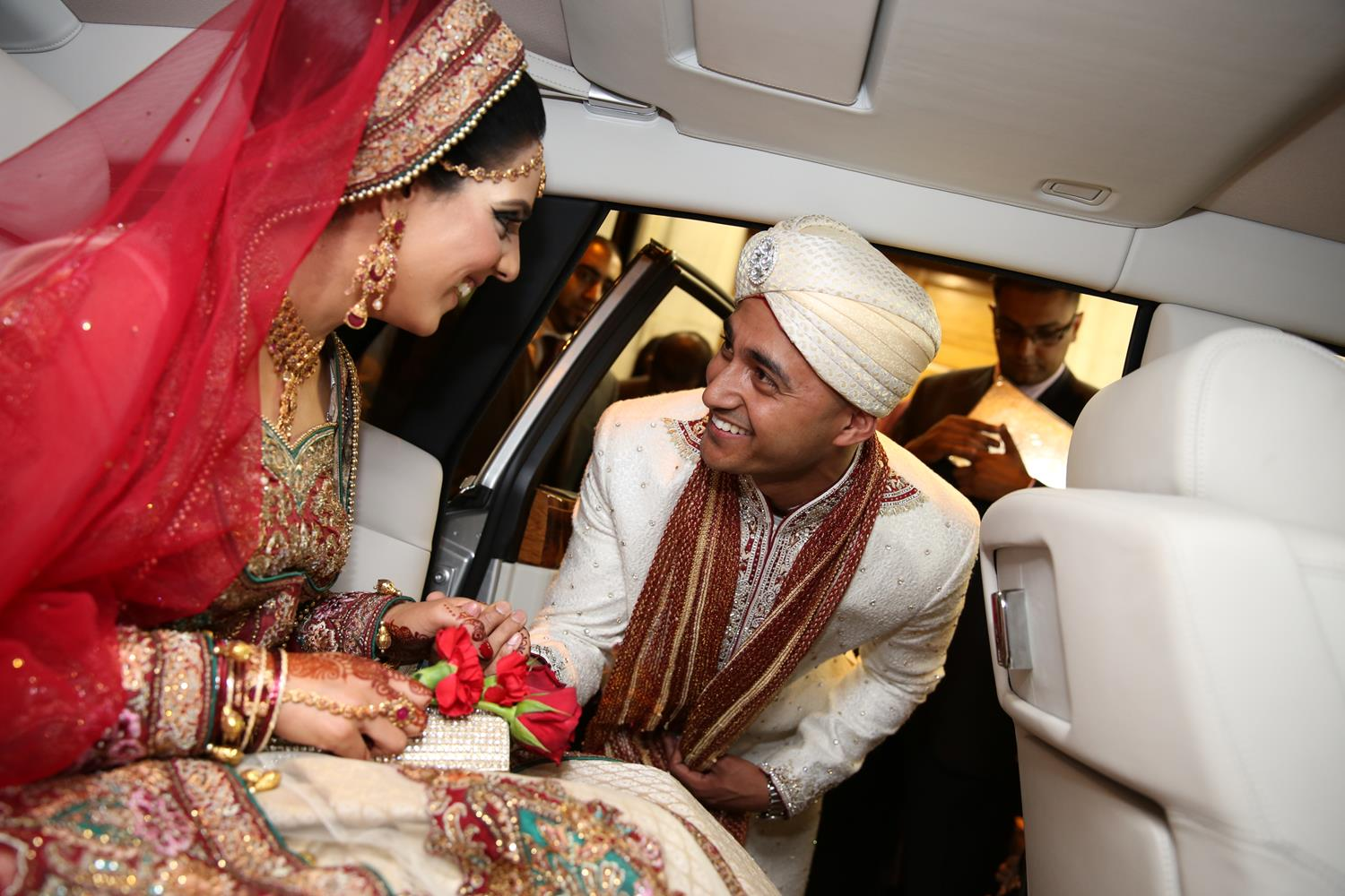 Wedding Photography of groom greeting bridge in car arriving at their Indian Wedding by MAKSAM Photography London