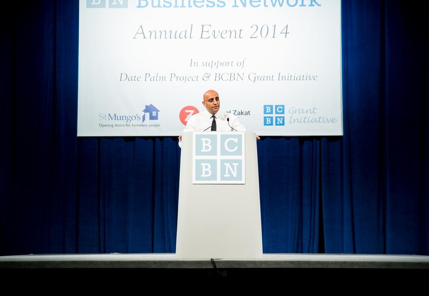 Corporate Event Photography of man on podium taken by MAKSAM Corporate photographer