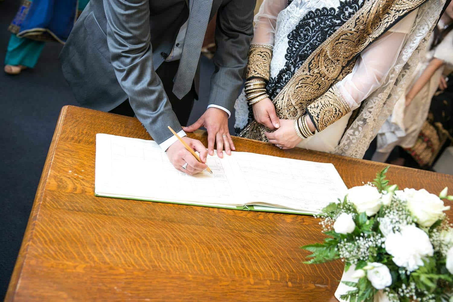 Registry Photography of couple signing book by MAKSAM Photography