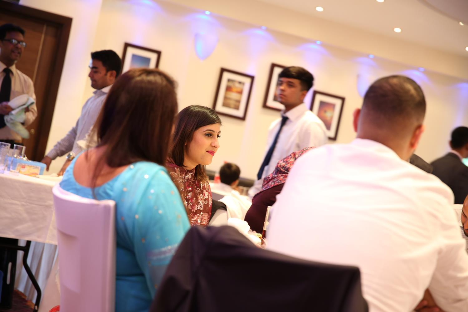 People sitting down at an Indian Wedding Dinner by MAKSAM Photography